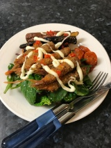 Salt and pepper crumbed prawns, colourful carrots cherries on a bed of salad with mayo and chilli sauce