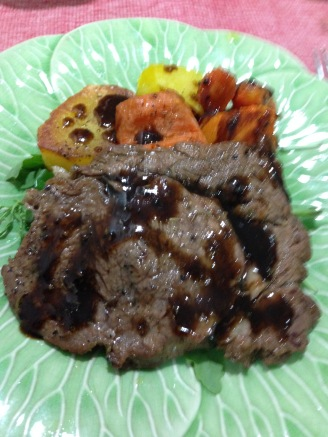 Herbs and balsamic cream bbq ribeyes steak on a bed of rockets served with roasted vegetables.jpg